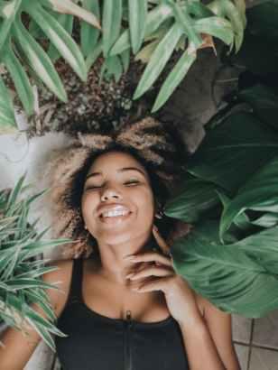 cheerful woman resting in plant nursery