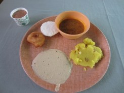 Mein Frühstück, bestehend aus einem kleinen Becher Chai, einer scharfen Suppe, einem süßen Fruchtmousse, einer herzhaften Soße, einem frittierten Etwas und ein Brot, was nach gar nichts schmeckt.