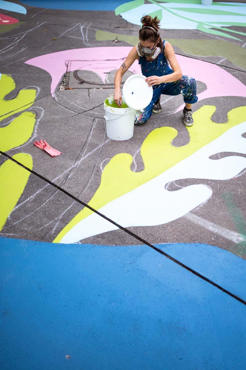 Peinture réalisée avec Hypermur, à l'angle de la rue Charles Hermite et de l'avenue de la Porte d'Aubervilliers, Paris 18e. L'artiste Cécilio peint un trottoir de 300m2. Photographie prise par Claire Jaillard.