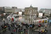 People walk next to giant dominos near Brandenburg Gate in Berlin