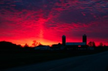Vibrant red sunset with farm buildings in silhouette