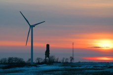Wind turbine and old grain elevator at sunset