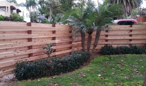 Knotty Western Red Cedar decking is installed horizontally on top of 4x4 posts to create a beautiful good neighbor fence