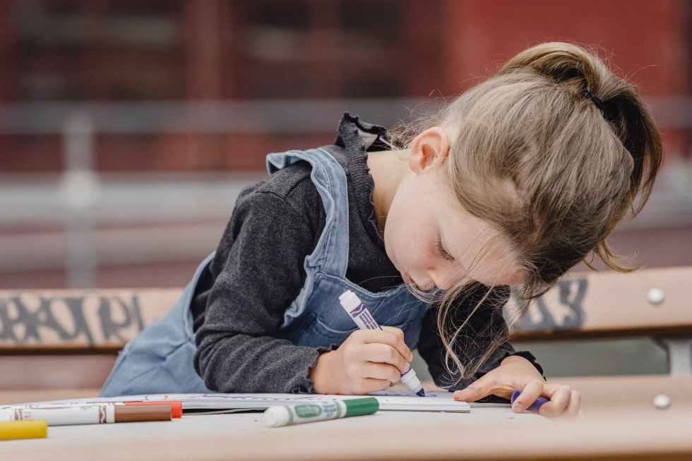 focused little girl drawing on paper