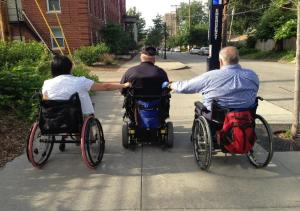 A man in a power wheelchair pulls a man and a woman in manual wheelchairs behind him.