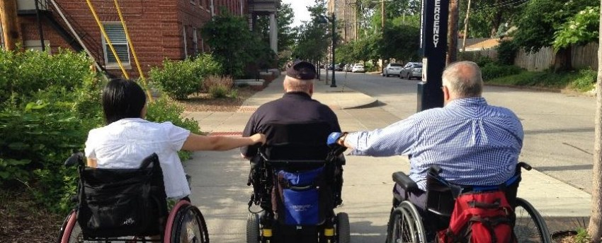 A man and a woman in manual wheelchairs hold on to the back of a man's power wheelchair as he gives them a ride down a city sidewalk