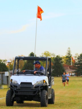 Racers follow a Polaris Ranger along Cedarville's cross country track in the Fall Costume 5K Oct. 23.
