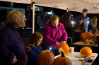 Students carve pumpkins during the Oct. 30 ALT Night. Students looked up carving designs on their phones and used their phones as flashlights to illuminate their pumpkin carvings.