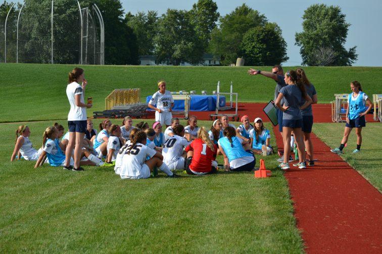 Coach Jonathan Meade gives instructions to the Lady Jacket huddle. (Photo: Andriana Polsdorfer)