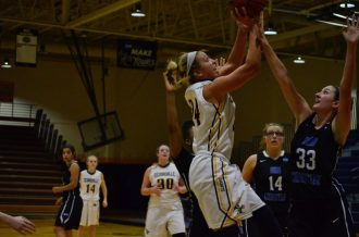 Kaitlyn Holm drives hard to the basket (Photo: Allyson Weislogel).