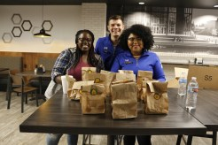 SCAB workers greet and hand out BIll's pumpkin doughnut holes to students in Stinger's, where Remember The Titans would be shown at 7:30. Left to right: SGA vice president, senior Mojade Adejokun; junior Ryan Smith, and Campus Community Committee leader, junior Indhira Adames.