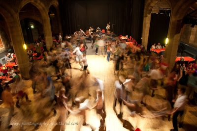 Ceilidh dancers in a large hall