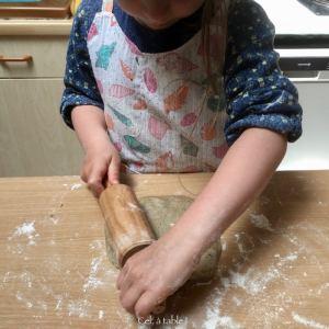 enfant qui étale pâte avec rouleau à pâtisserie dans différentes directions