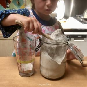 un enfant qui transvase de la farine de sarrasin dans un verre à mesurer