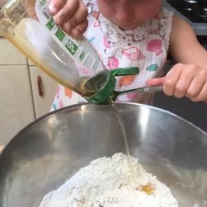 enfant qui mesure une cuillère à café de sirop d'agave pour pâte à pizza