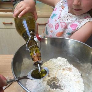 enfant qui verse une cuillère à soupe d'huile pour pâte à pizza