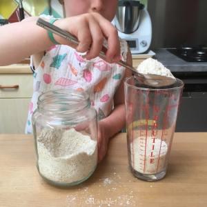 enfant qui mesure de la farine