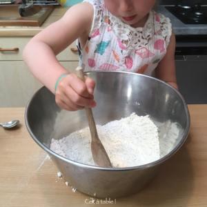 enfant qui mélange tous les ingrédients secs pour une pâte à pizza