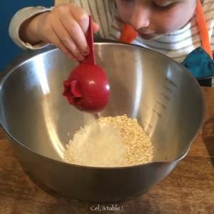enfant qui verse de la noix de coco dans un saladier
