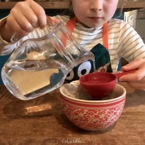enfant qui verse de l'eau avec un pichet