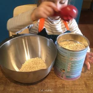 enfant qui remplis une tasse avec des flocons d'avoine