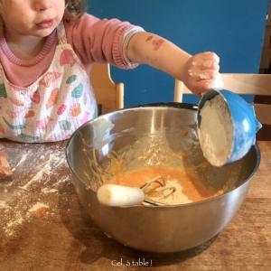 enfant qui verse de la farine dans un saladier