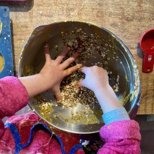 enfant qui mélange à la main du crumble