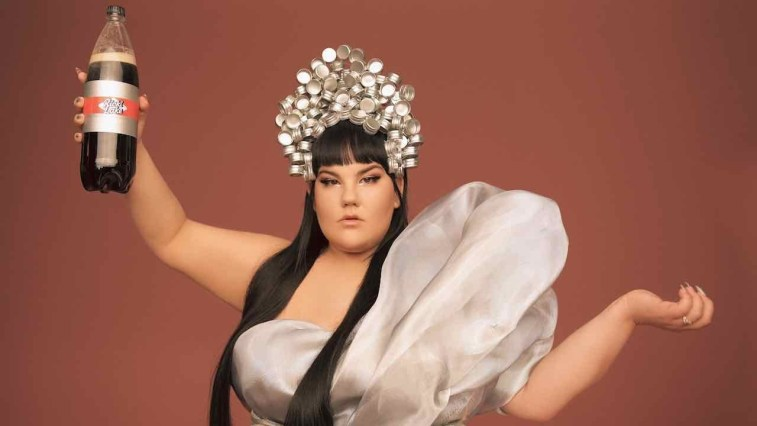 "Netta wearing a silver crown and a silver dress with a big shoulder-padded strap, holding up what looks like a big bottle of Diet Coke but actually has the words ""Ricki Lake"" branded on it."