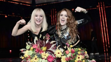 Winners of Melodifestivalen 2020, Anna Bergendahl and Dotter, celebrating their wins with raised arms and flowers on a table in front of them.