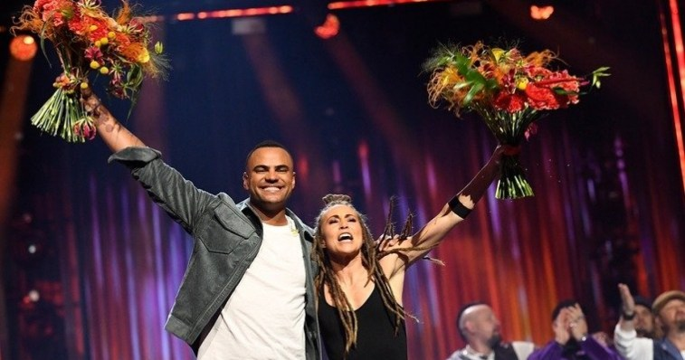 Mohombi and Mariette hugging whilst holding their flowers up high in celebration of their win on the Melodifestivalen 2020 stage