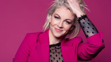 Lesley Roy dressed in a pink jacket against a purple background, holding her grey-blonde hair up.