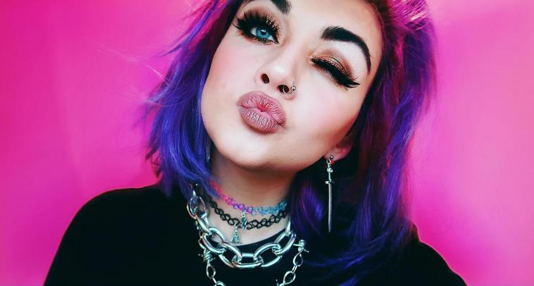 "Bronnie promo pic for ""Over You"" which sees her winking at the camera, pouting, with her purple hair cut in a bob. She's wearing a black top and chain necklaces with a pink backdrop."
