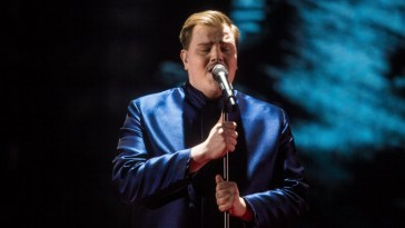 "Aksel wearing a blue jacket over a black top, singing his song ""Looking Back"" on a stage at Finland's national selection show for Eurovision 2020."