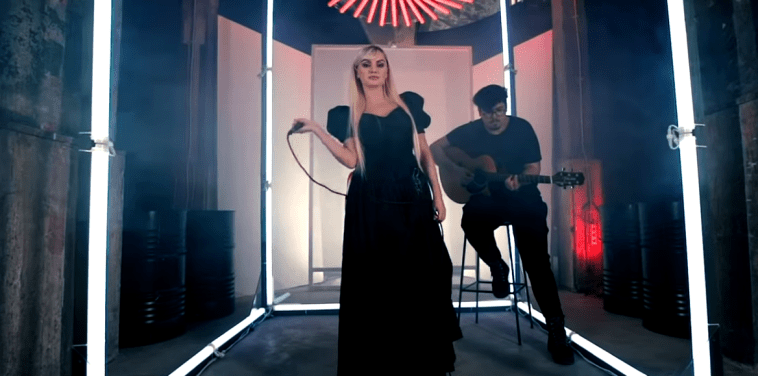 """Alexandra Stan performing in the video for """"Take Me Home"""" with Mircea Steriu behind playing the guitar."""