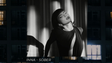 "Single cover artwork for ""Sober"" which sees INNA wearing a black dress and lying back which is hung as a backdrop over a block of flats."