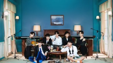 BTS gathered in a room with instruments for the concept cover of their new album BE
