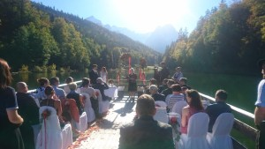 picture of a raft floating on a glacial lake in Germany and which has a wedding Celebrant at the front, speaking in front of 25 wedding guests and the wedding couple.