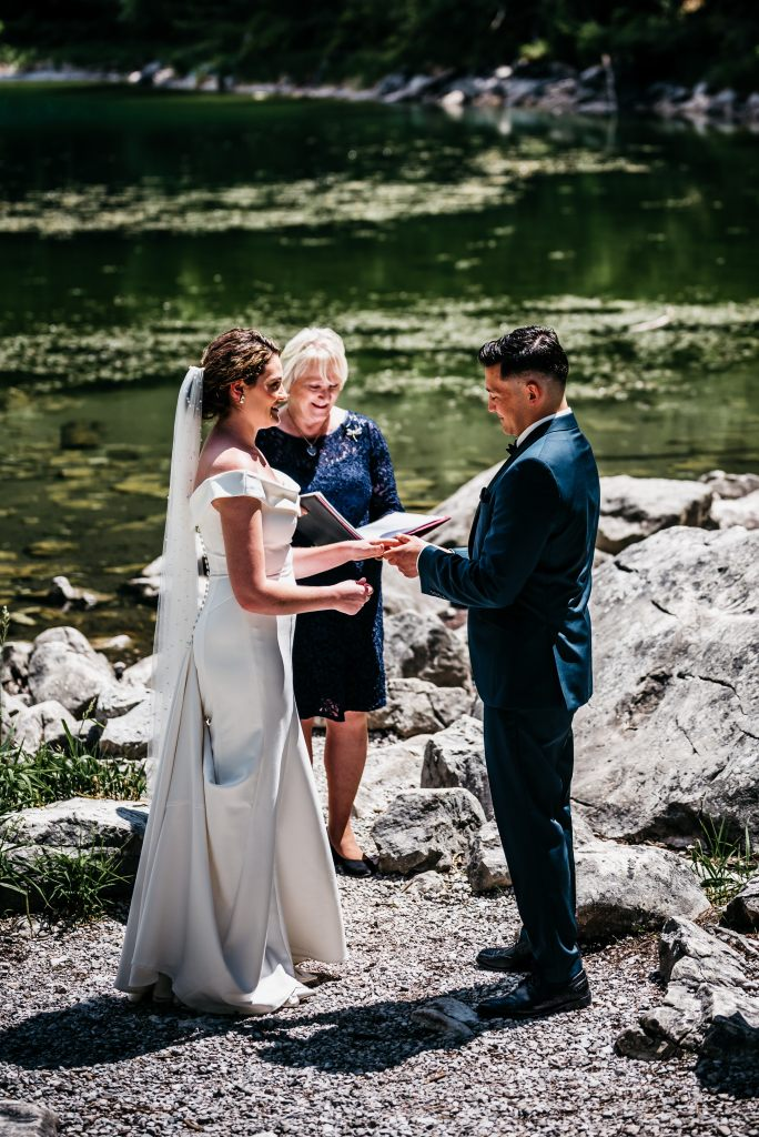 Celebrant and couple are holding their elopement ceremony next to a mountain lake.