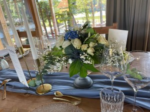 BLUE AND CREAM FLOWERS ON A TABLE WITH A BLUE CLOTH AND LUXURY CHINA AND GLASSWARE SET FOR A WEDDING BREAKFAST