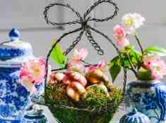 DIY Gold Easter Eggs in a moss-lined basket with blue and white ginger jars in background