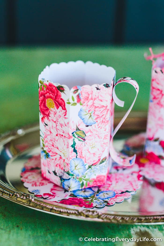 floral paper teacup on a silver tray on a green table