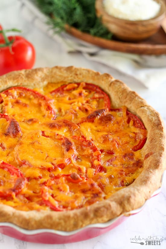Savory Tomato Cheddar Pie - A buttermilk biscuit crust holds layers of freshly sliced tomatoes, cheddar and parmesan cheeses, and a creamy dill and scallion filling. This flavorful savory pie can be served for any meal of the day.