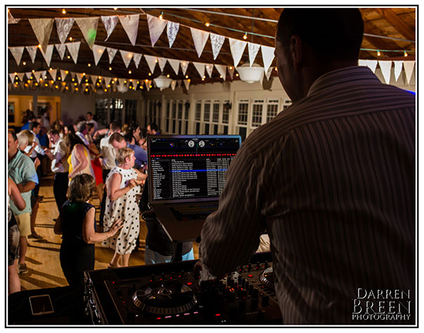 A DJ plays music during a wedding reception. Learn more about Celebrity Productions, your online event planner and DJ entertainment guru.