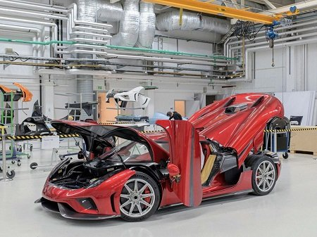 A red Koenigsegg Regera at the factory in Angelholm, all separable parts lifted..