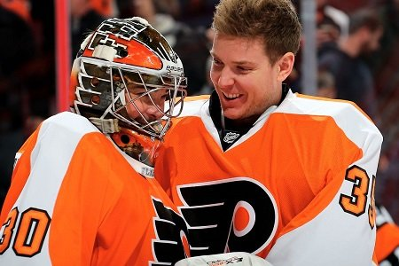 Michal Neuvirth (left) with helmet on being joked by Steve Mason (right) without a helmet.