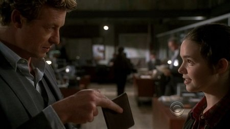The scene where Patrick Jane (Simon Baker) teaches Anne (Madison McLaughlin) how to pickpocket. Simon holding a wallet in front of Madison, pictured sideways.