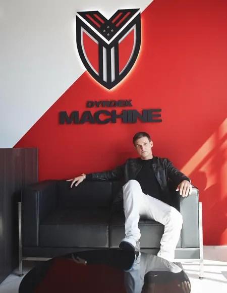 Rob Dyrdek's 'Dyrdek Machine' houses all his business ventures. He sitting on one side of a sofa with the 'Dyrdek Machine' trademark behind him.