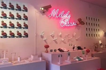 Melody Ehsani written in neon lights inside her store.
