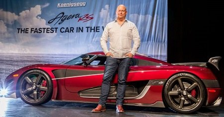 Christian von Koenigsegg standing in front of the fastest car in the world, Koenigsegg Agera RS in red color, at the Canadian International Auto Show in Toronto.