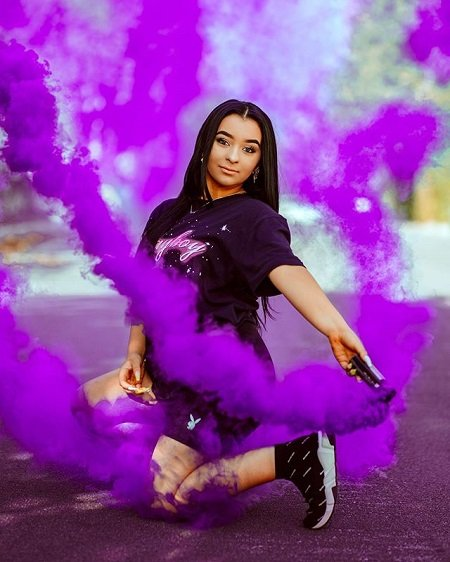 Danielle Cohn using a purple flare for a pose photo.